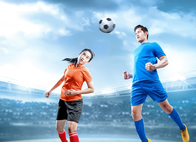 El jugador de fútbol asiático salta y se enfrenta en duelo con la pelota en el aire en el campo de fútbol