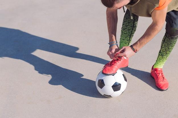 Jugador de fútbol atando botas con un pie en la pelota