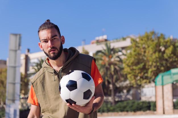 Jugador de fútbol atractivo con una pelota en la mano