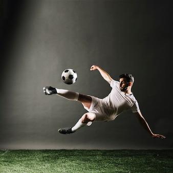 Jugador de fútbol barbudo cayendo y pateando la pelota