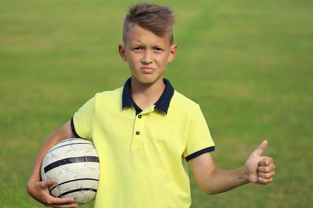 Jugador de fútbol de chico guapo en una camiseta amarilla sostiene el balón en su mano. la segunda mano muestra los pulgares hacia arriba