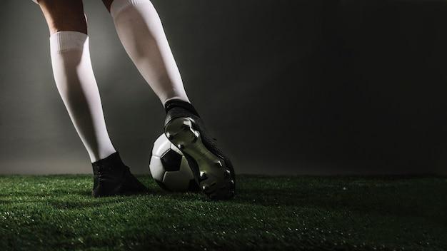 Jugador de fútbol de cultivo pateando la pelota