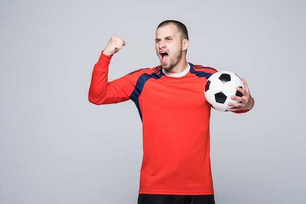 Jugador de fútbol emocionado en camiseta roja sosteniendo un concepto de victoria de fútbol aislado en blanco