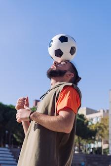 Jugador de fútbol equilibrando el balón en la cabeza.