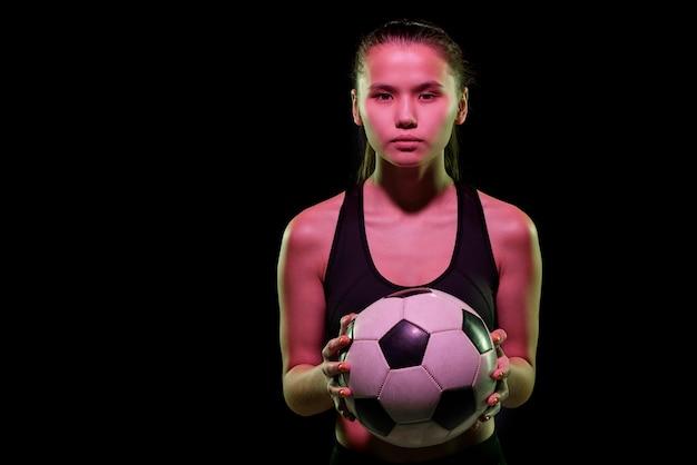 Jugador de fútbol femenino bastante joven que sostiene el balón de fútbol mientras entrena en aislamiento delante de la cámara sobre fondo negro