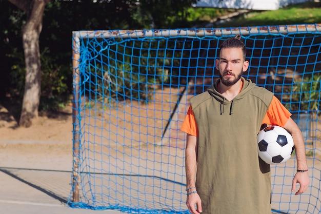 Jugador de fútbol frente a la portería con el balón.