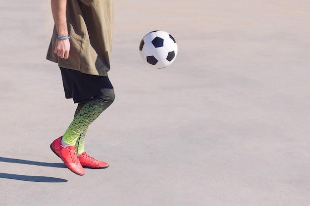 Jugador de fútbol irreconocible jugando a la pelota