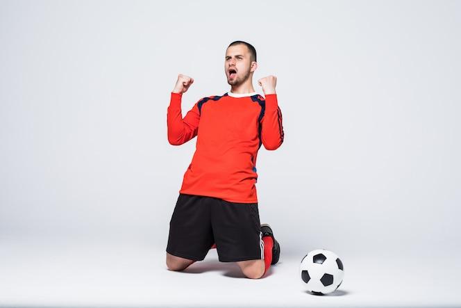 Jugador de fútbol joven y emocionado en camiseta roja celebrando el gol de gol