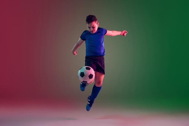 Jugador de fútbol masculino adolescente en pared degradada en luz de neón