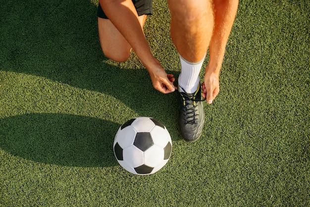Jugador de fútbol masculino ata los cordones de los zapatos en las botas, vista superior. futbolista en el estadio al aire libre, entrenamiento antes del juego, entrenamiento de fútbol