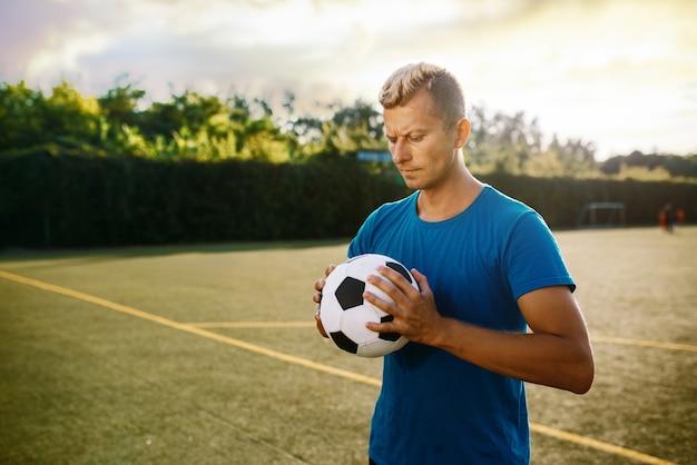 Jugador de fútbol masculino con balón en las manos en el campo. futbolista en el estadio al aire libre, entrenamiento antes del juego, entrenamiento de fútbol