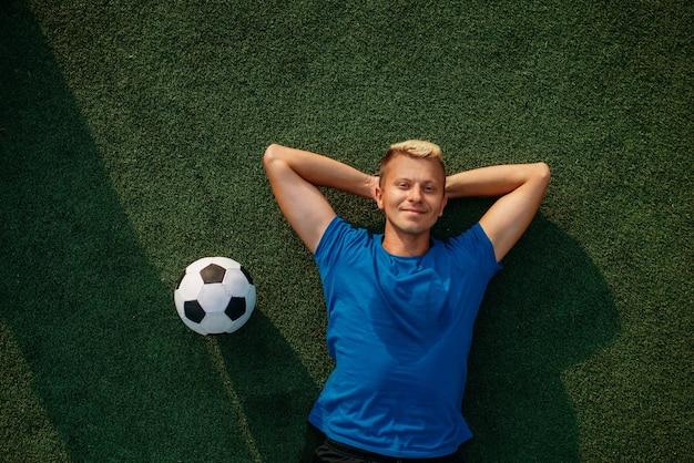 Jugador de fútbol masculino con balón tirado en el césped en el campo, vista superior. futbolista en el estadio al aire libre, entrenamiento antes del juego, entrenamiento de fútbol