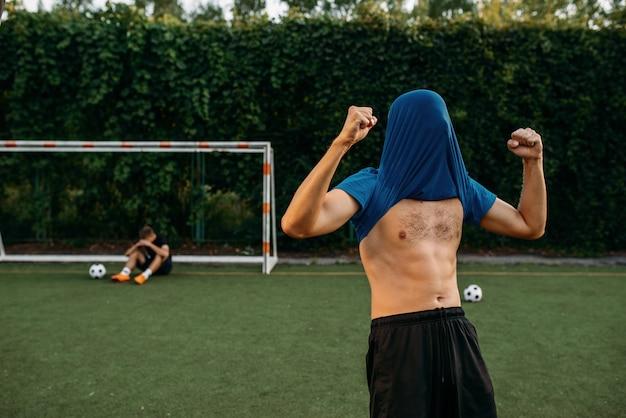 Jugador de fútbol masculino golpea la meta en el campo. futbolistas en el estadio al aire libre, entrenamiento antes del juego, entrenamiento de fútbol