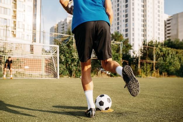 Jugador de fútbol masculino golpea la pelota en el campo. futbolista en el estadio al aire libre, entrenamiento antes del juego, entrenamiento de fútbol