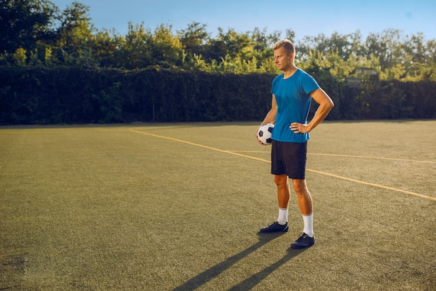 Jugador de fútbol masculino con pie de pelota en el campo. futbolista en el estadio al aire libre, entrenamiento antes del juego, entrenamiento de fútbol