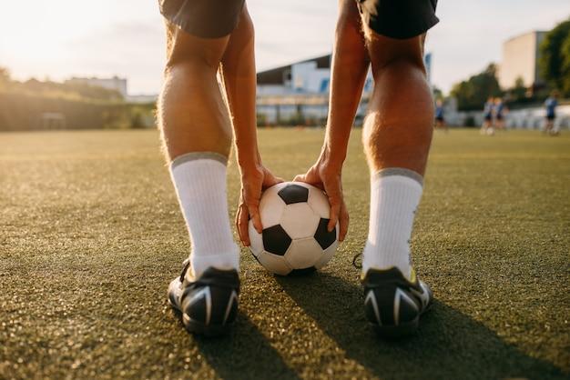 Jugador de fútbol masculino se prepara para golpear la pelota en el campo. futbolista en el estadio al aire libre en un día soleado, entrenamiento antes del juego, entrenamiento de fútbol