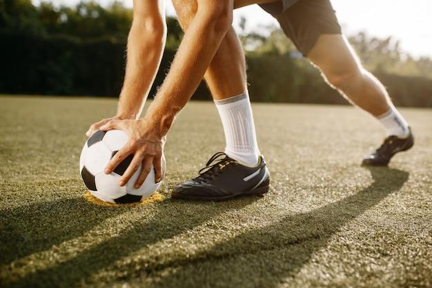 Jugador de fútbol masculino se prepara para golpear la pelota en el campo. futbolista en el estadio al aire libre, entrenamiento antes del juego, entrenamiento de fútbol