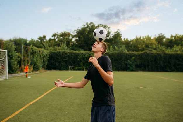 Jugador de fútbol masculino rellena el balón con la cabeza en el campo. futbolistas en el estadio al aire libre, entrenamiento del equipo antes del juego