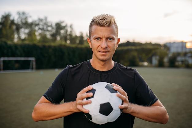 Jugador de fútbol masculino sosteniendo la pelota en las manos en el campo. futbolista en el estadio al aire libre, entrenamiento antes del juego, entrenamiento de fútbol