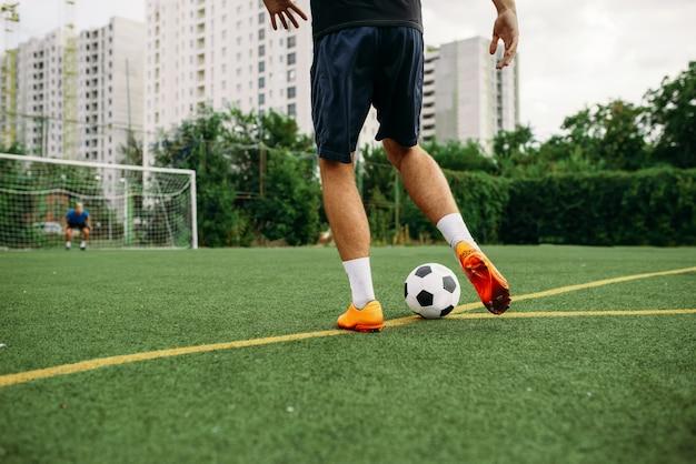 Jugador de fútbol masculino trabajando con balón en el campo. futbolista en el estadio al aire libre, entrenamiento antes del juego, entrenamiento de fútbol