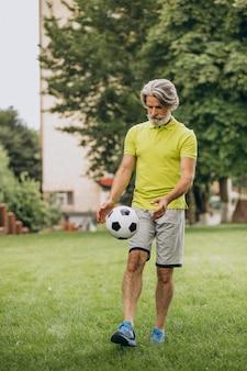 Jugador de fútbol de mediana edad con pelota de fútbol