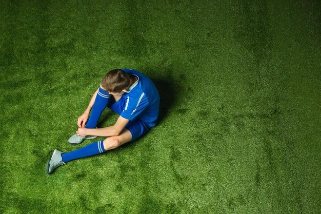 Jugador de fútbol de niño sentado en la hierba verde