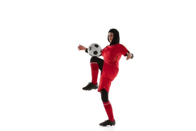 Jugador de fútbol o fútbol femenino árabe aislado sobre fondo blanco de estudio. mujer joven pateando la pelota, entrenando, practicando en movimiento y acción.