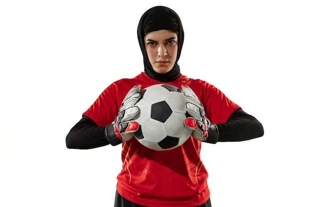 Jugador de fútbol o fútbol femenino árabe, portero sobre fondo blanco de estudio. mujer joven posando confiada con balón, protegiendo goles para el equipo.