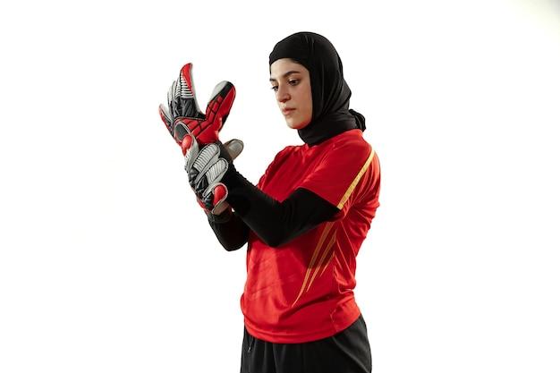 Jugador de fútbol o fútbol femenino árabe, portero sobre fondo blanco de estudio. mujer joven preparándose para el juego, entrenamiento, protegiendo los objetivos del equipo. concepto de deporte, afición, estilo de vida saludable.