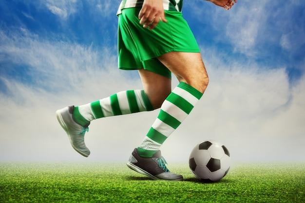 Jugador de fútbol pasando la pelota en el campo de fútbol al aire libre