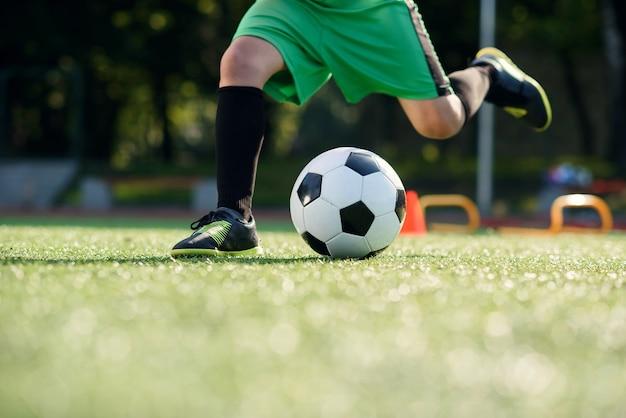 Jugador de fútbol pateando la pelota en el campo. jugadores de fútbol en sesión de entrenamiento. cerrar los pies del futbolista pateando la pelota sobre el césped.