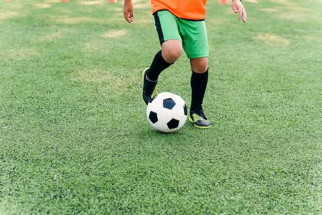 Jugador de fútbol pateando la pelota en el campo. jugadores de fútbol en sesión de entrenamiento.