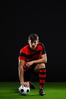 Jugador de fútbol pateando la pelota, jugando al fútbol