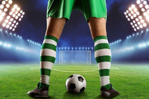 Jugador de fútbol con una pelota entre las piernas de pie en el campo de fútbol