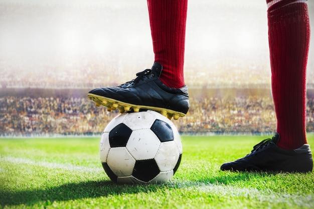 Jugador de fútbol de pie con balón de fútbol patada en el estadio