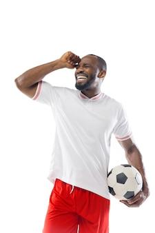 Jugador de fútbol profesional aislado en la pared blanca del estudio
