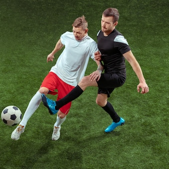 Jugador de fútbol que aborda la pelota sobre fondo de hierba verde.