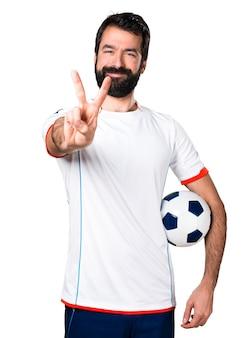 Jugador de fútbol que sostiene un balón de fútbol que hace gesto de la victoria