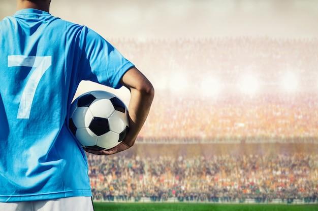 Jugador de fútbol soccer en concepto azul del equipo que sostiene el balón de fútbol