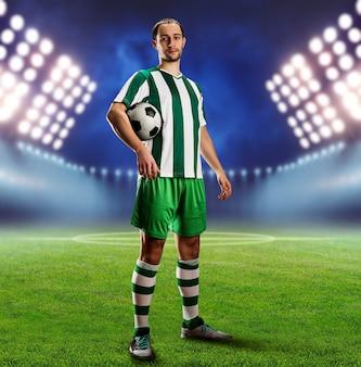 Jugador de fútbol sosteniendo una pelota en el campo de fútbol por la noche