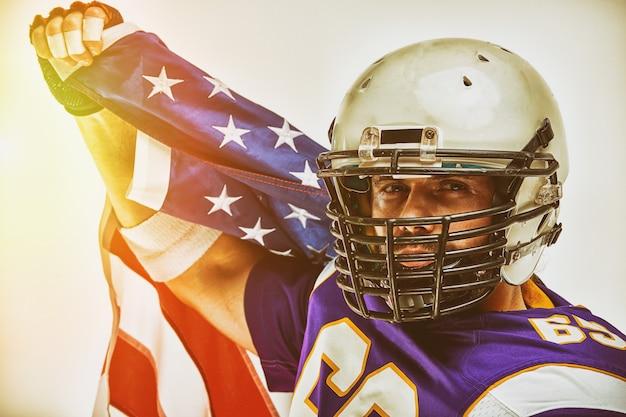 Jugador de fútbol con uniforme y una bandera americana celebra la victoria, en un espacio en blanco.