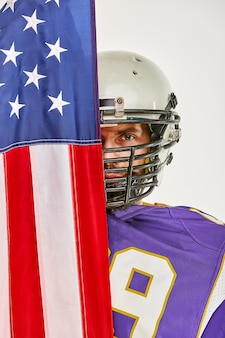 Jugador de fútbol con uniforme y una bandera estadounidense orgullosa de su país,