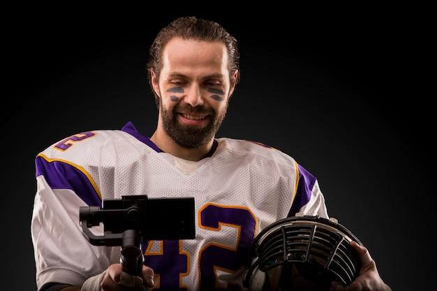 Jugador de fútbol con un uniforme blanco haciendo una selfie en un espacio oscuro.
