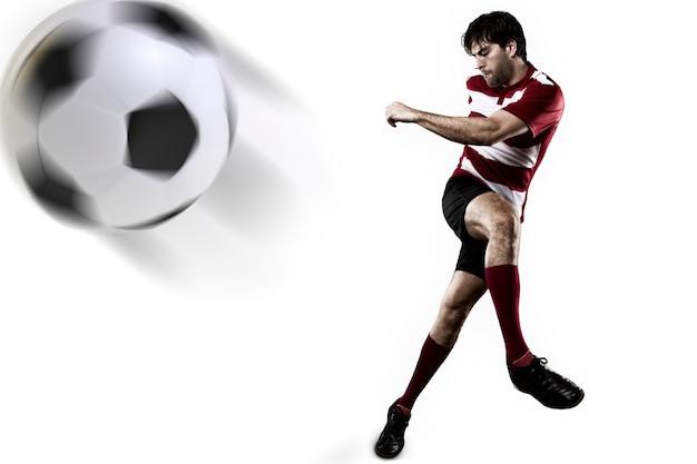 Jugador de fútbol con un uniforme rojo pateando.