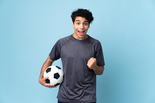 Jugador de fútbol venezolano hombre sobre antecedentes aislados celebrando una victoria en la posición ganadora