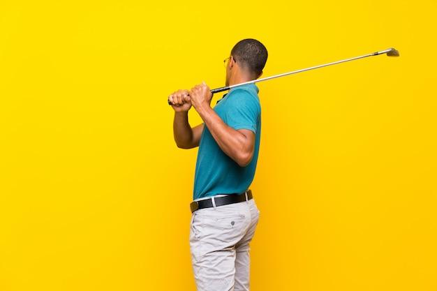Jugador de golf afroamericano hombre sobre pared amarilla aislada