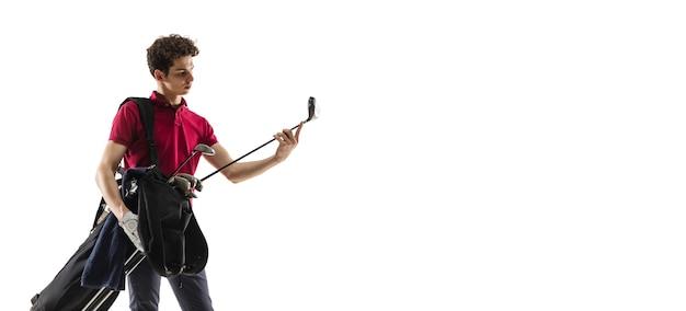 Jugador de golf en una camisa roja tomando un swing en estudio blanco