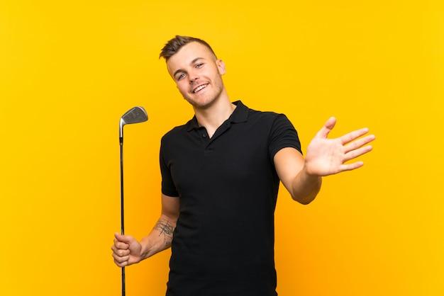 Jugador de golfista hombre sobre pared amarilla aislada saludando con la mano con expresión feliz