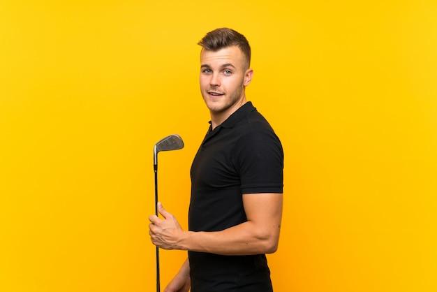 Jugador de golfista hombre sobre pared amarilla aislada sonriendo mucho