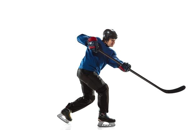 Jugador de hockey femenino joven con el palo en la cancha de hielo y pared blanca